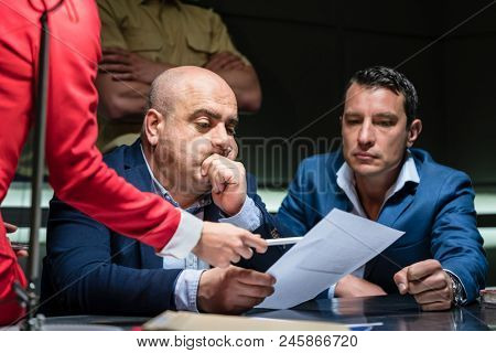 Portrait of a middle-aged man calling his attorney in order to ask for legal assistance, under the pressure of a difficult interrogation at the police