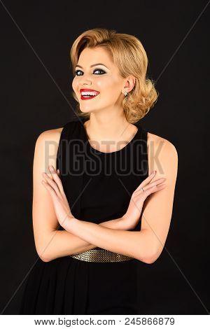 Blonde Girl With Evening Makeup Posing On Black Background. Smiling Blonde Girl In Black Evening Dre