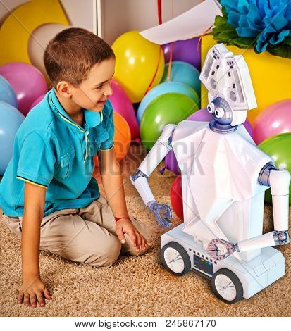 Child playing with robot toy. Girl is programming own tech smart toys with artificial intelligence at school. Kid play in kids club indoor primary school. Kindergarten boy sit on floor with balloon