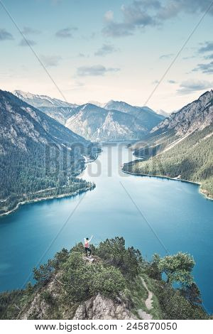 Happy female adventurer with backpack and arm raised enjoying amazing view to mountain lake in valley from top of mountain after summer hike - adventure, travel and hiking concept. Plansee, Austria