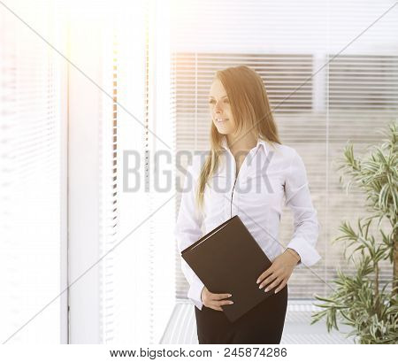 Successful Business Woman With Clipbord Standing In A Modern Office.photo With Place For Text