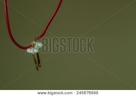 Copper alloy electrical contacts in white hard plastic insulator with red wire attached to each lead. poster