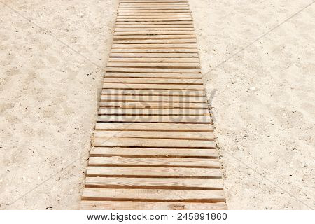 Wooden Beach Boardwalk With Sand For Background.
