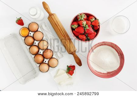 Flat Lay Set Raw Ingredients For Cooking Strawberry Pie Or Cake On White Background. Eggs, Flour, Mi