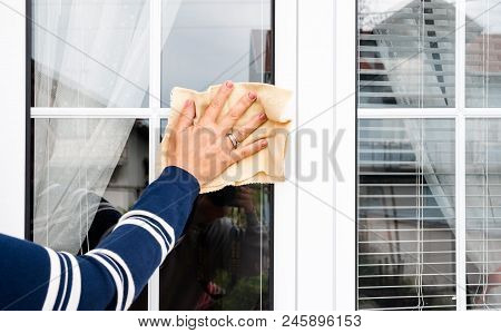 Woman Hand With Rag Cleaning White Pvc Window