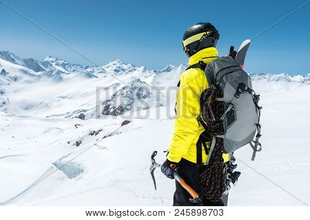 A Mountaineer Man Holds An Ice Ax High In The Mountains Covered With Snow. View From The Back. Outdo