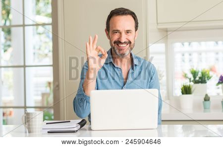 Middle age man using laptop at home doing ok sign with fingers, excellent symbol