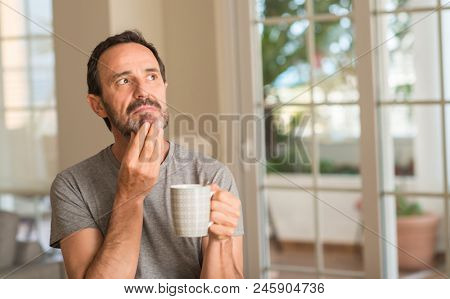 Middle age man drinking coffee in a cup serious face thinking about question, very confused idea