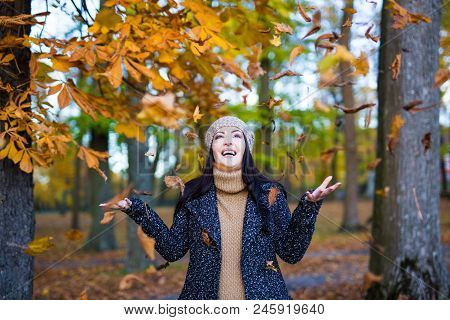 Autumn Concept - Portrait Of Happy Woman Throwing Leaves In Park