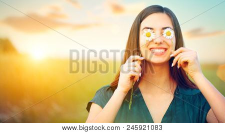 Beauty joyful girl with daysy flowers on her eyes enjoying nature and laughing on summer field. Beautiful young woman having fun. Sunflare, sunbeams, glow sun. Healthy people, happy, good mood