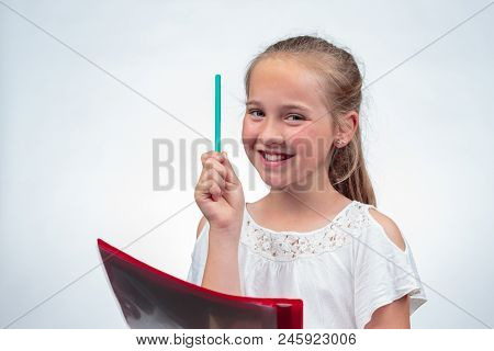 A Cute 10-year-old Caucasian Schoolgirl Smiling While Holding Up A Pencil In The Air And Her Note Pa