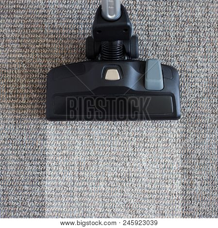 Housekeeping Before And After Concept - Modern Vacuum Cleaner Over Dirty Carpet Floor