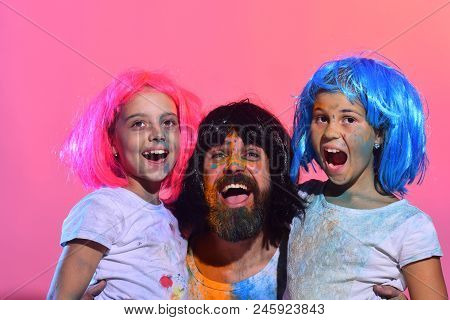 Girls And Guy With Excited Faces Hug On Pink Background. Kids And Bearded Man Wear Wigs. Children An