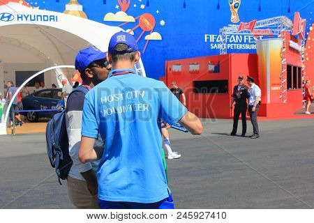 St. Petersburg, Russia - June 18, 2018: Fifa World Cup Russia 2018 Volunteer Helping A Fan. Male Vol