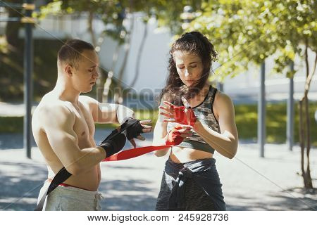 Athletic Caucasian Man And Woman Wrapping Hands With Bandages For Workout In Summer Park, Horizontal