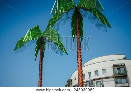 Artificial Green Metal Palms With White Living House And Blue Sky Background In Park Fiction Hamburg