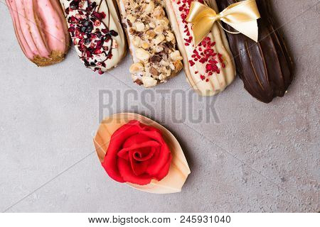 Sweet Delicious Colorful French Eclairs. Group Of French Dessert With Marzipan Rose. Eclair Backgrou