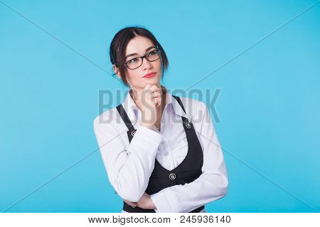 Portrait Of An Attractive Thoughtful Pensive Young Woman Wearing Glasses With Her Finger To Her Chin