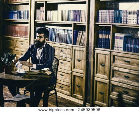 Aristocratic lifestyle concept. Man in classic suit sits in vintage interior, library, book shelves on background. Aristocrat on busy face pouring cup. Oldfashioned man holds cup with tea. poster