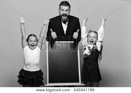 Kids Holding Hands Up Stand Next To Blackboard And Teacher, Copy Space. Girls And Man With Happy Fac