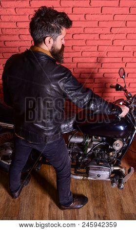 Man With Beard, Biker In Leather Jacket Near Motor Bike In Garage, Brick Wall Background. Masculine