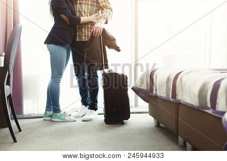 Unrecognizable Young Couple Arrived To Hotel Room On Honeymoon. Family Standing On Window Background