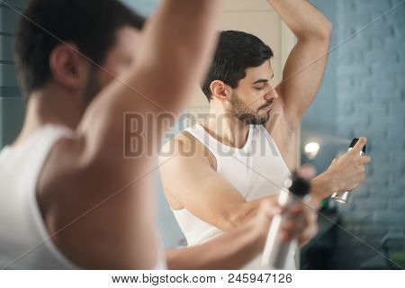 Young Hispanic People And Male Beauty. Confident Metrosexual Man Using Spray Deodorant On Underarm S
