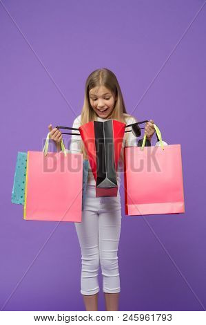 Child Look In Shopping Bags On Violet Background. Little Shopaholic Smile Surprised With Paper Bags.
