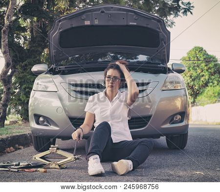 Woman Sitting On Ground And Using Mobile Phone Near Her Car Broken Down On The Road Side.