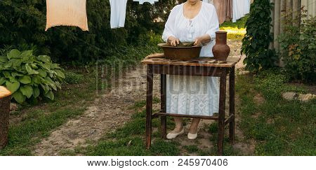 An Elderly Woman Is Washing Clothes In The Garden. In White Vintage Clothing. Country Life. Clothes