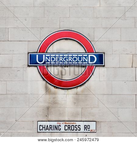 London, UK - 8 June 2017: The iconic sign for the London Underground on a wall in Charring Cross Road, Westminster.  In London, England.