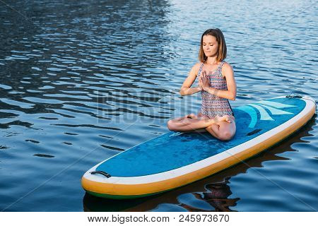 Young Woman Meditating On Paddle Board. Practice Yoga On Paddle Board, Woman Sitting On Paddle Board