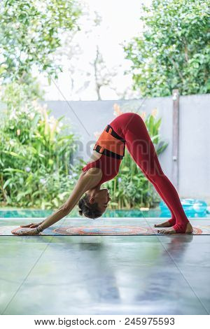Side View Of Fit Young Woman Practicing Yoga In Downward-facing Dog Adho Mukha Svanasana Pose