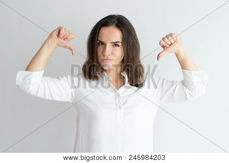 Content Girl In White Shirt Proud Of Herself. Young Caucasian Woman Pointing Both Thumbs At Herself.