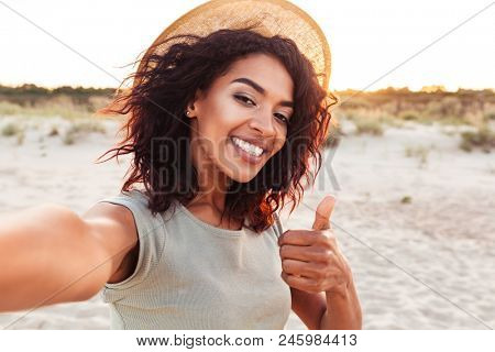 Close up of cheerful young african girl in summer hat taking a selfie at the beach and showing thumbs up gesture