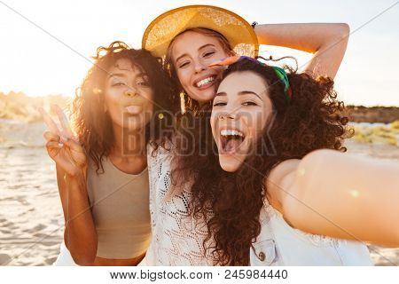 Three positive multiethnic women 20s in summer clothing smiling at camera while taking selfie photo during holiday on nature