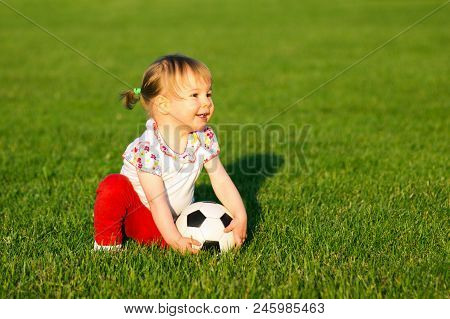 The Smiling Little Cute Baby Girl Is Playing With Small Soccer Ball For Children On Green Grass Play