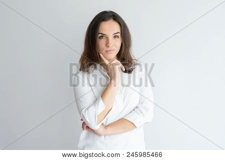 Pensive grinning girl thinking over decision. Young Caucasian woman in white blouse leaning chin on hand and posing. Decision making concept poster
