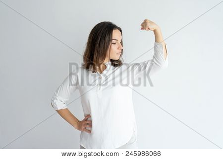 Serious Proud Girl Showing Strength Gesture. Young Caucasian Woman In White Blouse Flexing Hand Musc
