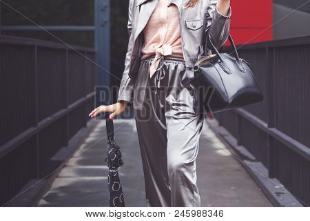 Trendy Woman In Silver Pants Jacket With Black Leather Hand Bag And Umbrella. Fashionable Outfit.
