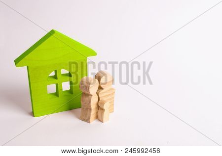 Figures Of People Stand Near A Wooden House On A White Background. A Young Family Is Standing Near T