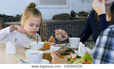 Family Have Healthy Lunch At Restaurant. Little Daughter Eating Vegetable