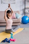 beautiful young woman practicing yoga in lotus pose with namaste gesture at home poster