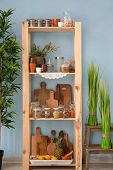 Wooden storage stand with kitchenware and different foodstuff indoors poster