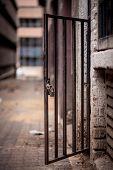 A metal doorway with padlock stands open in a dirty alleyway. Johannesburg inner city poster