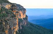 Large rocky cliffs and characteristic blue haze in the Blue Mountains National Park, Australia. poster