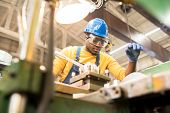 Serious busy young black factory engineer in hardhat and safety goggles examining milling lathe and repairing it while working at production plant poster