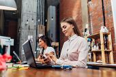 Friendly female office workers wearing formal workwear typing on laptop keyboard working in creative agency. poster