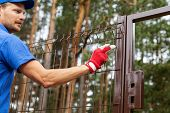 territory enclosure - worker installing metal fence poster