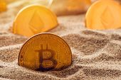 Golden bitcoin in sand, conceptual image for lost and found valuable cryptocurrency coins that are standing the test of time. poster